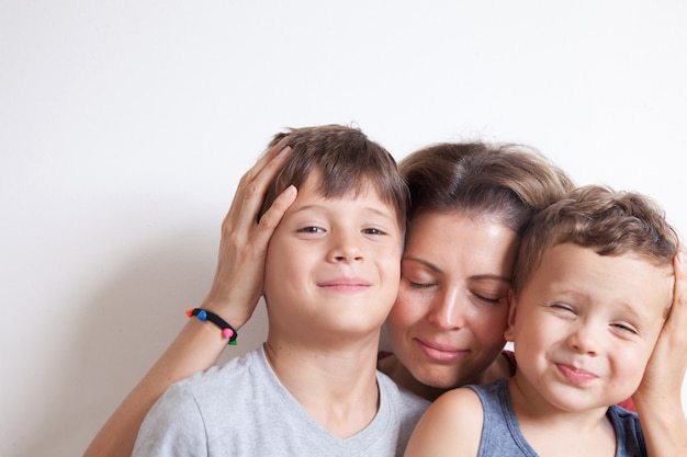 Portrait of happy mother with cute kids boy on a light wall. happy family concept.