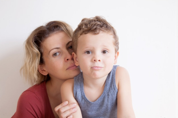 Portrait of happy mother with cute kids boy sitting on a light background. happy family concept.
