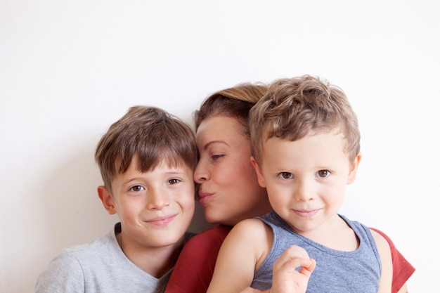 Portrait of happy mother with cute kids boys sitting on a light background. happy family concept.