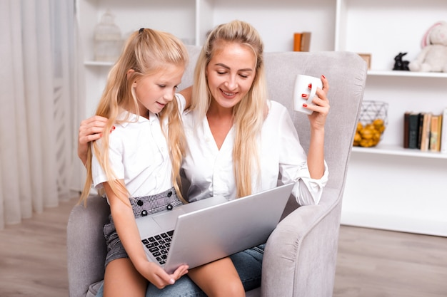 Portrait of happy mother working online with laptop while sitting at home with her cute daughter.