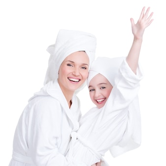 Portrait of happy mother and young daughter in white dressing gown and towel- isolated. happy family people concept.
