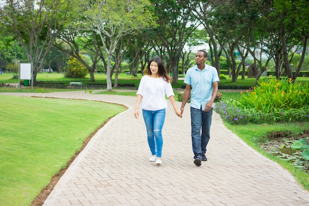 Portrait of happy multiethnic couple walking together in park.