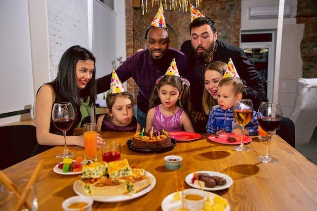 Ritratto di famiglia multietnica felice che celebra un compleanno a casa. grande famiglia che mangia snack e beve vino mentre saluta e si diverte i bambini. celebrazione, famiglia, festa, concetto di casa.