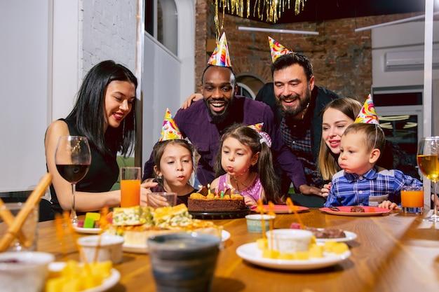 Ritratto di famiglia multietnica felice che celebra un compleanno a casa