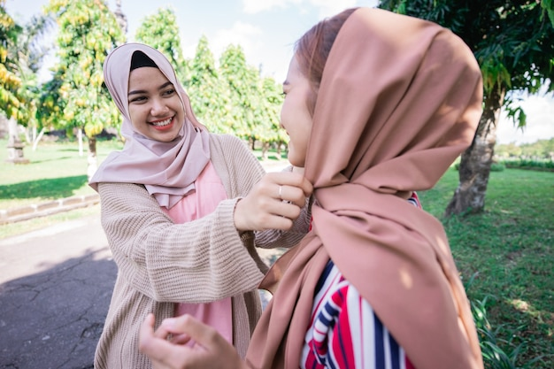Portrait of happy muslim asian woman fixing friend hijab while meeting outdoor