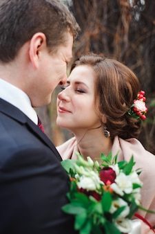 Portrait of happy newlyweds in autumn nature.