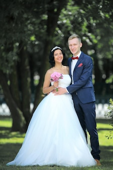 Portrait of happy newlyweds on the background of the park