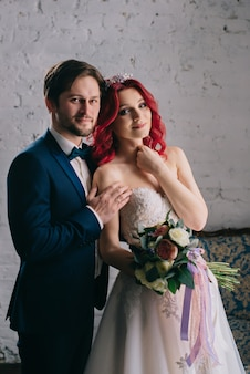 Portrait of happy newlyweds who laugh and cuddle in a loft-style room