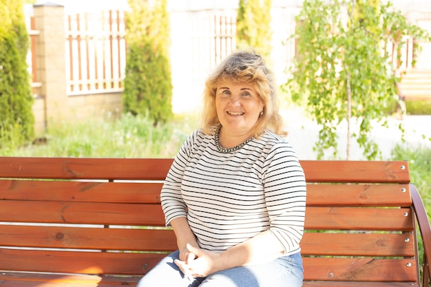 Portrait of happy older woman sitting on a bench outside in summer