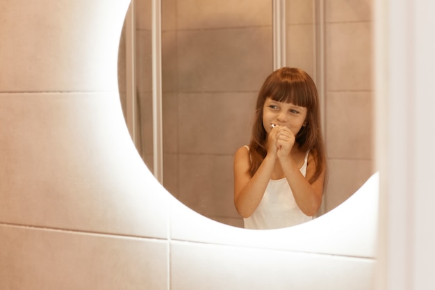 Portrait of happy optimistic little female kid brushing teeth in bathroom, standing in front of the mirror, having positive facial expression, enjoying hygienic procedures.
