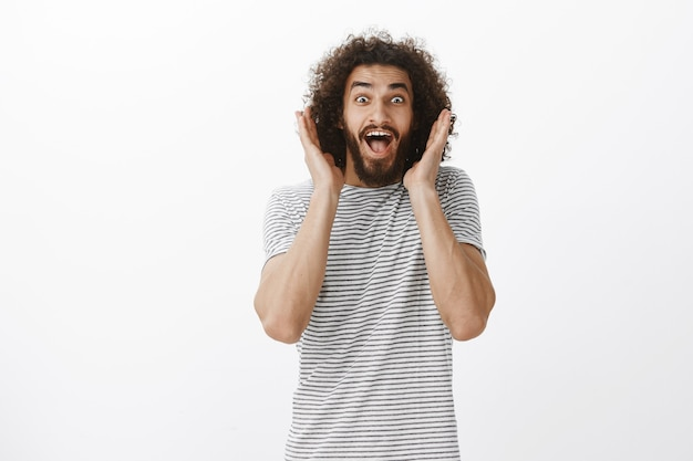 Portrait of happy overwhelmed handsome male model with beard and curly hair, screaming from surprised and positive emotions, holding palms near face