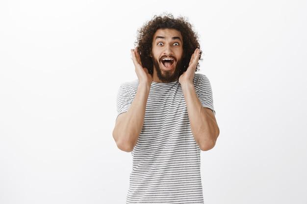 Ritratto di felice modello maschio bello sopraffatto con barba e capelli ricci, urlando da emozioni sorprese e positive, tenendo le palme vicino al viso