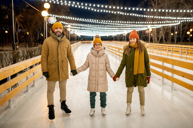 Portrait of happy parents with daughter holding hands while skating together in the park