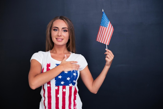 Portrait of a happy patriotic girl holding usa flag on gray space