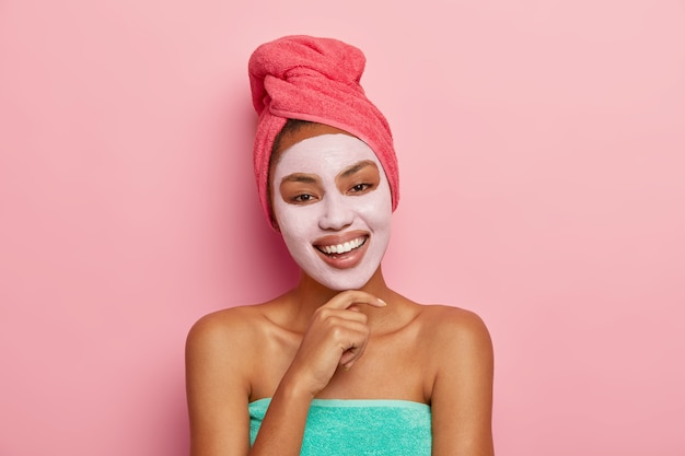 Portrait of happy pleased woman with facial clay mask, tilts head and touches chin, wrapped in towel, cares about beauty, smiles happily and shows white teeth