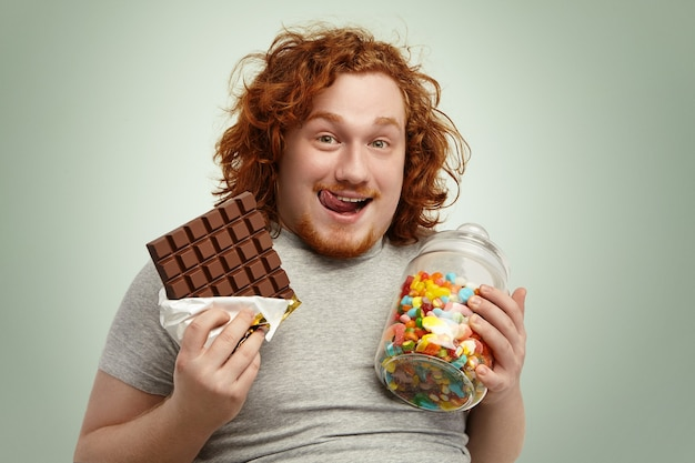 Portrait of happy plump young redhead bearded man looking at camera with cheerful expression