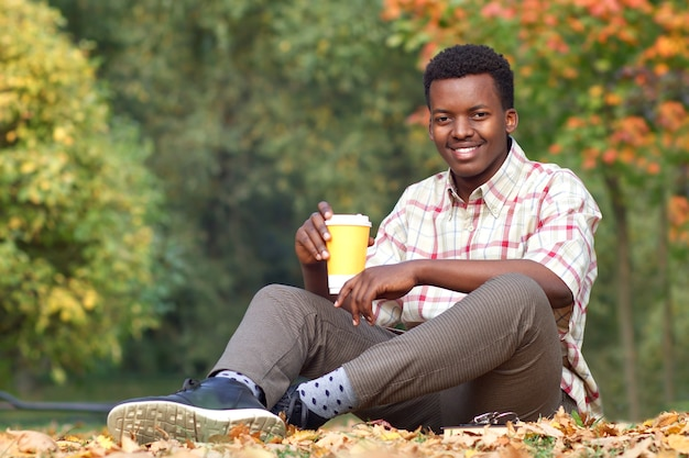 Portrait of happy positive black african afro american young handsome man sitting on the grass in golden autumn park, smiling, drinking a hot drink tea or coffee from plastic cup
