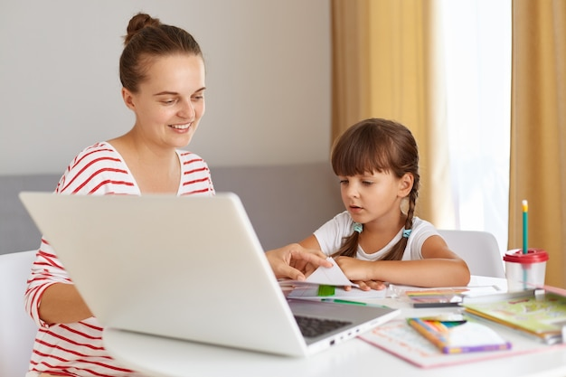 Portrait of happy positive female with daughter wearing casual attire, sitting at table against of window in living room, doing homework, mother helping child with online lesson.