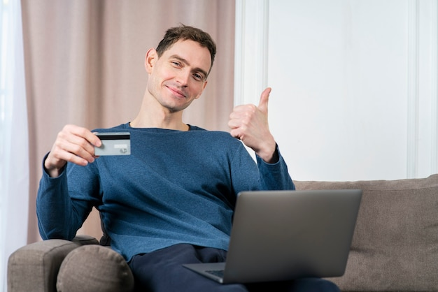 Portrait of happy positive guy young handsome man holding in hand credit bank card and laptop
