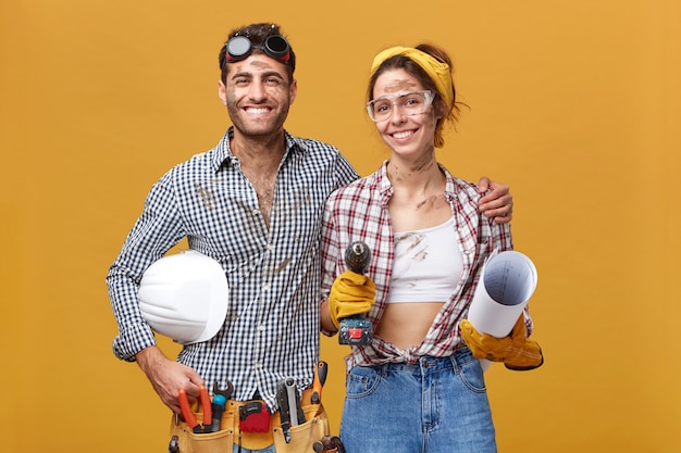Portrait of happy positive maintenance employees working together: cheerful male wearing belt kit with tools embracing cute woman with drill and blueprint, standing close to each other