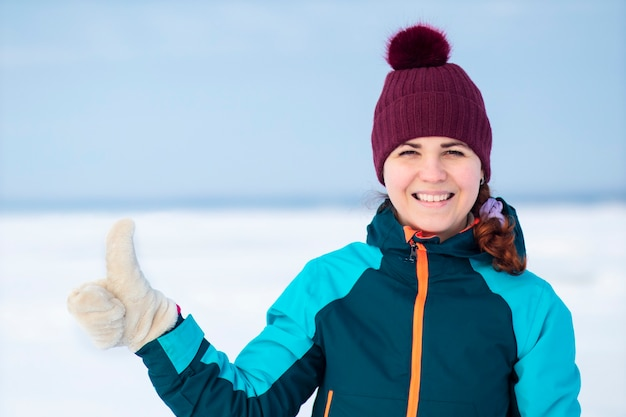 Portrait of happy positive young woman in winter warm clothes