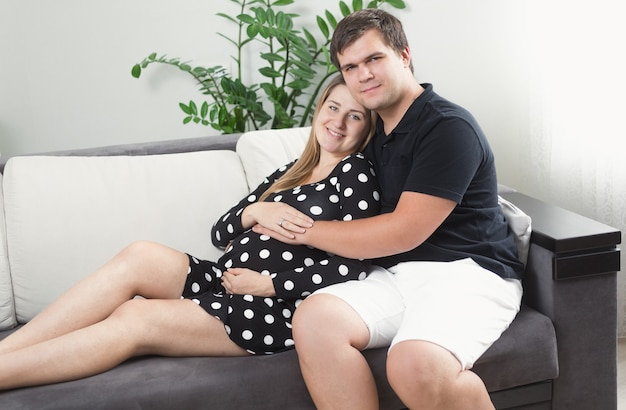 Portrait of happy pregnant woman and man relaxing on sofa at living room