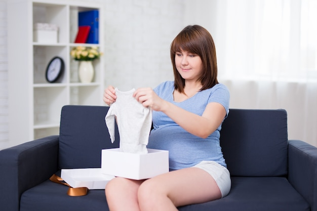 Portrait of happy pregnant woman opening gift box for baby