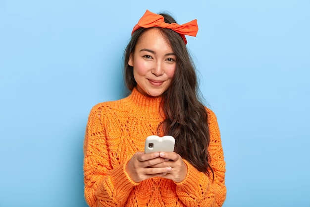 Portrait of happy pretty asian woman with long hair, wears headband and orange sweater, holds mobile phone for chatting, downloads new application