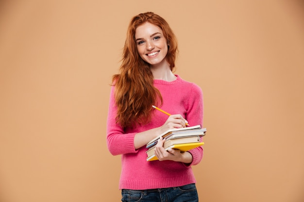 Portrait of a happy pretty redhead girl holding books