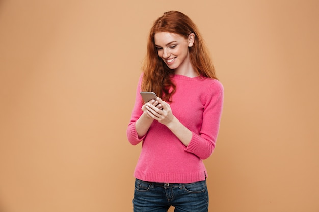 Portrait of a happy pretty redhead girl texting on smartphone