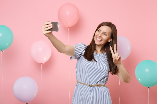 Portrait of happy pretty woman in blue dress doing selfie on mobile phone showing victory sign on pink background with colorful air balloons. birthday holiday party, people sincere emotions concept.