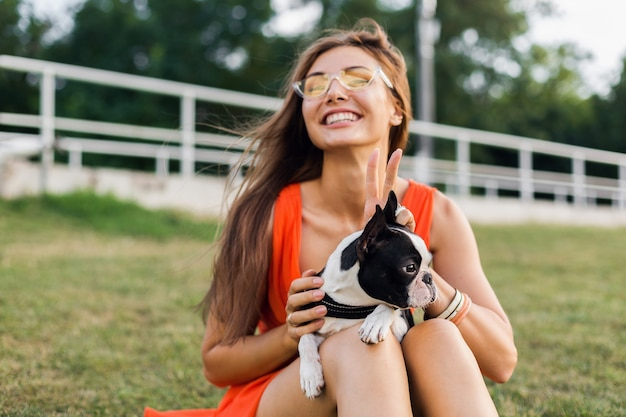 Portrait of happy pretty woman sitting on grass in summer park, holding boston terrier dog, smiling positive mood, wearing orange dress, trendy style, sunglasses, playing with pet