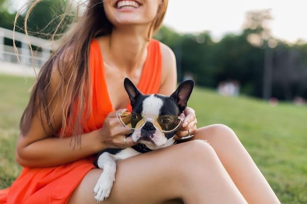 Ritratto di felice bella donna seduta sull'erba nel parco estivo, tenendo il cane boston terrier, sorridente stato d'animo positivo, indossa un abito arancione, stile alla moda, occhiali da sole, giocando con animali domestici