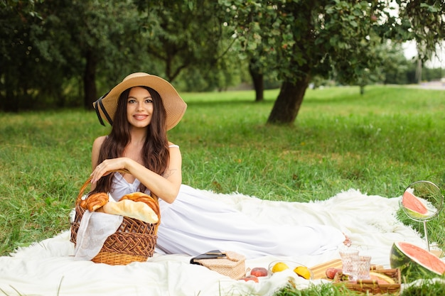 Portrait of happy pretty young lady in hat having rest on picnic in park while holding a basket of bread in hands