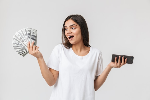 Portrait of a happy pretty young woman casualy dressed isolated on white, showing money banknotes, using mobile phone