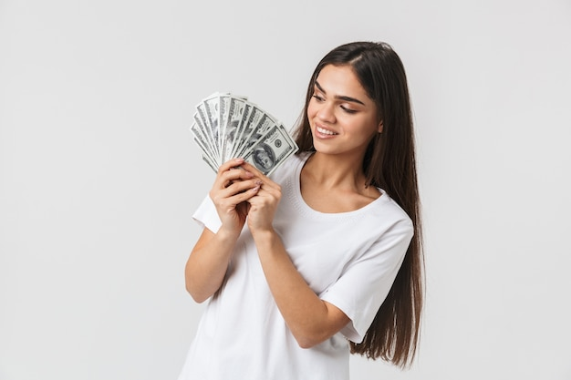Portrait of a happy pretty young woman casualy dressed isolated on white, showing money banknotes