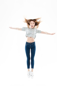 Portrait of a happy pretty young woman jumping with hands raised