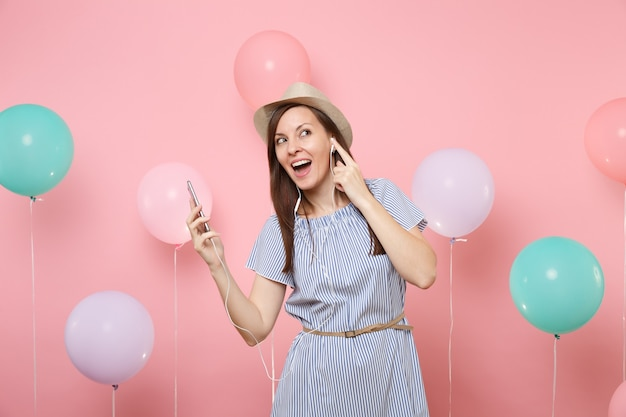 Portrait of happy pretty young woman in straw summer hat and blue dress with mobile phone and earphones listening music on pastel pink background with colorful air balloons. birthday holiday party.