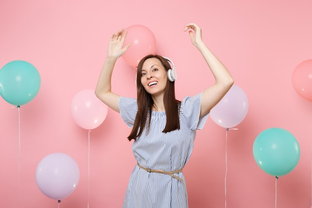 Portrait of happy pretty young woman with headphones in blue dress listening music dancing on pastel pink background with colorful air balloons. birthday holiday party people sincere emotions concept.