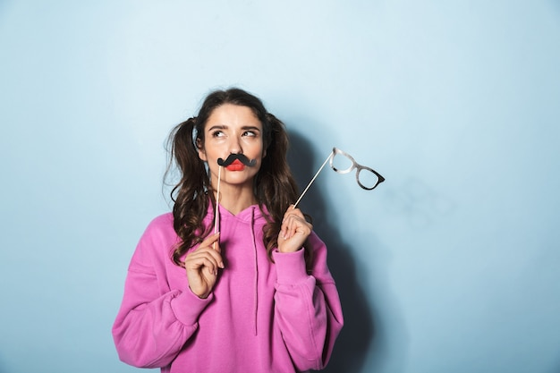 Portrait of happy princess girl holding paper mustache and fake sunglasses on stick over blue in studio
