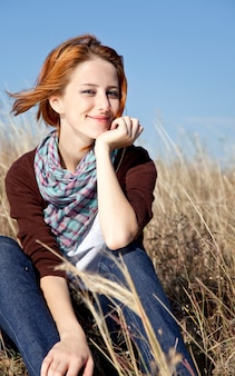 Portrait of happy red-haired girl on autumn grass.