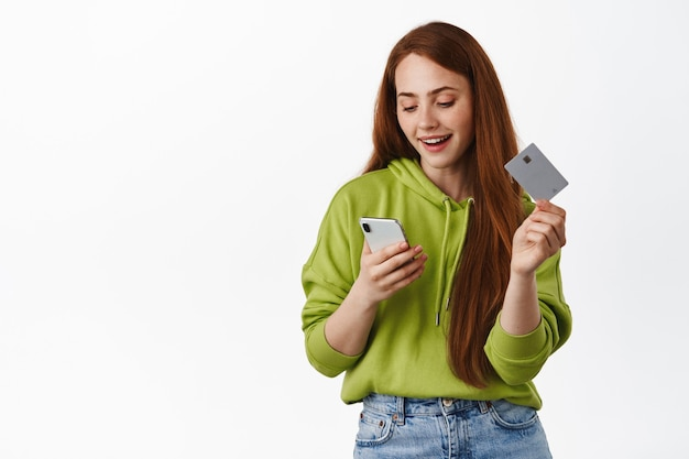 Portrait of happy redhead woman holds credit card, looking at smartphone while order in app, buying something in internet on white.