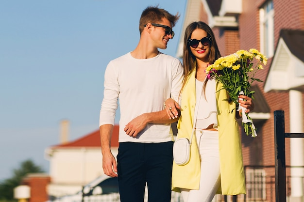 Portrait of a happy romantic couple embracing  outdoors in european city at the evening. young pretty woman holding flowers. couple in love dating.