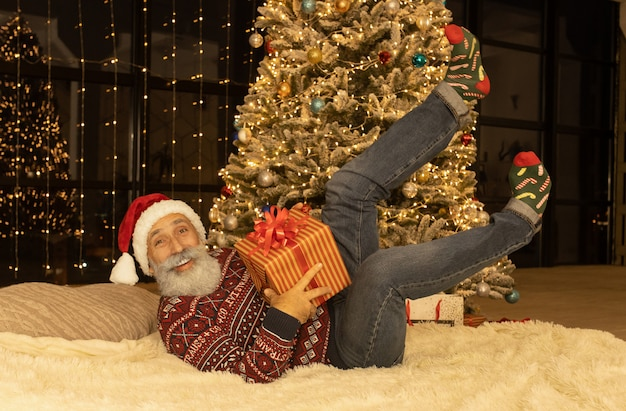 Portrait of happy santa claus at his room at home near christmas tree.