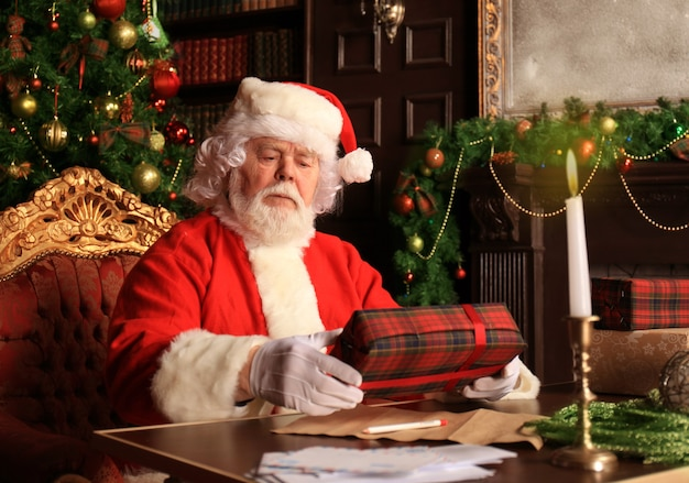 Portrait of happy santa claus sitting at his room at home near christmas tree with gift box.
