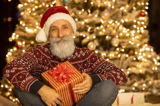 Portrait of happy santa claus sitting at his room at home near christmas tree.