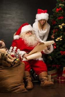 Portrait of happy santa claus with his helper reading christmas letter or wish list