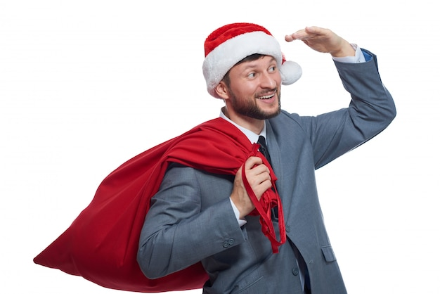 Portrait of happy santa claus with red full bag with presents, holding hand over eyes