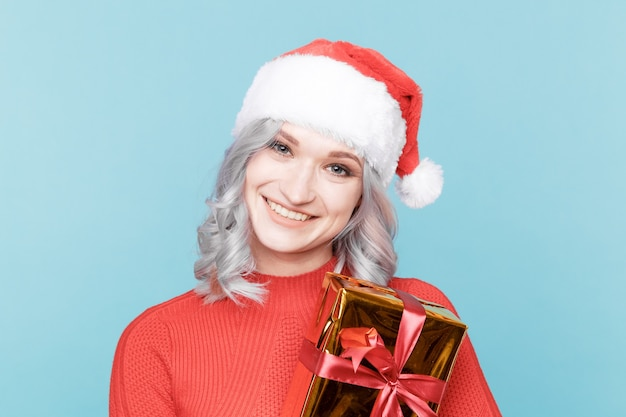 Portrait of happy santa woman hugs gift box isolated.