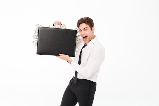 Portrait of a happy satisfied businessman showing briefcase